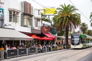 Tram passes cafes and diners on Acland Street, St Kilda